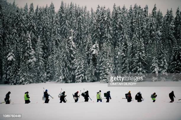 Anglers carry their gear as they walk through the snow to take position during the XVI World Ice Fishing Championship at the Shiroka Polyana dam near...