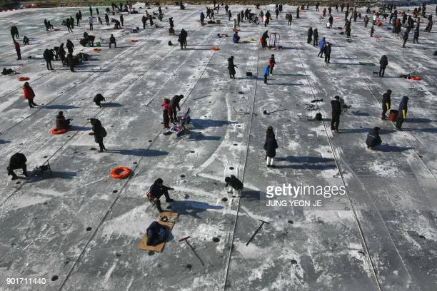 Anglers fish through holes created in the surface of a frozen river during the annual ice fishing festival in Hwacheon some 120 kilometers northeast...