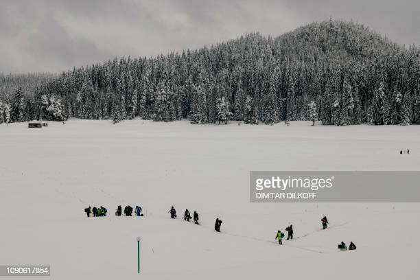 Anglers walk through the snow to take positions during the XVI World Ice Fishing Championship at the Shiroka Polyana dam near Batak on January 26...
