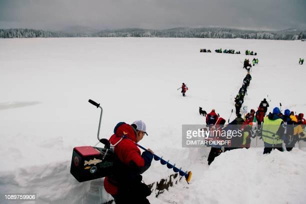 Anglers walk through the snow to take their positions during the XVI World Ice Fishing Championship at the Shiroka Polyana dam near Batak on January...