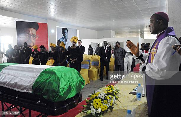 Anglican priest Owen Nwokolo prays near the casket of Professor Chinua Achebe on May 21 2013 at the Abuja airport The body of Achebe the author of...
