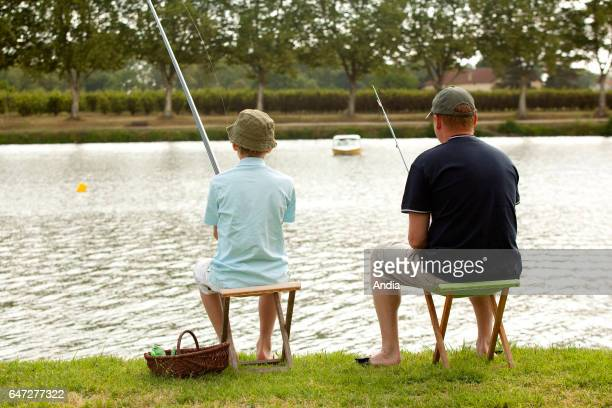 Angling close to the Bidounet Mill in Moissac in summer with a man and his father seated and angling by the Tarn river