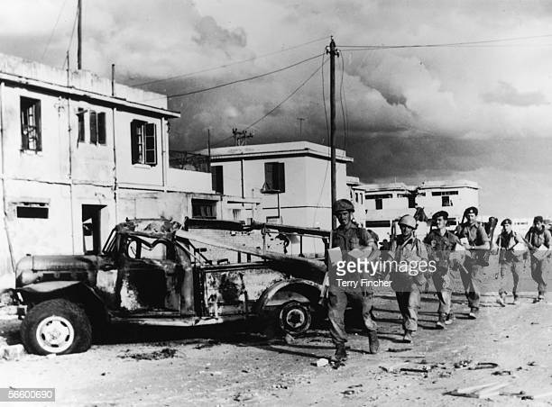 Anglo-French troops walking past a burned-out truck in Port Said, Egypt, during the Suez Crisis, 13th November 1956.