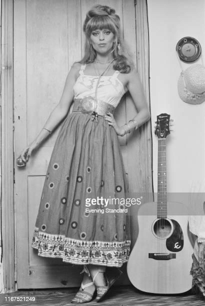 AngloHungarian fashion designer and actress Edina Ronay wearing long dress and sandals near an acoustic guitar UK 28th June 1976