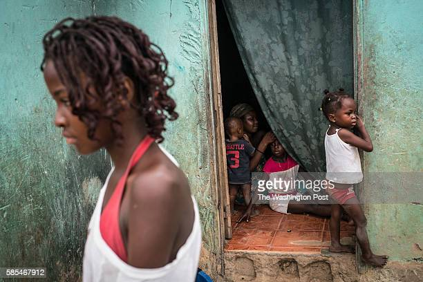 A mother braids her daughter's hair in a poor neighborhood overlooking Cabinda a heavily guarded territory that accounts for half the oil output from...