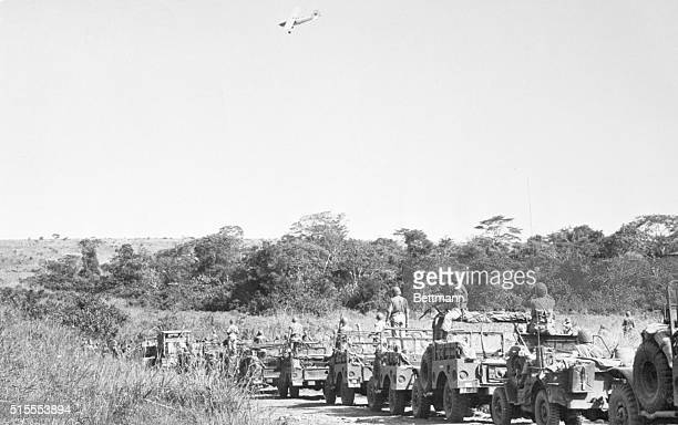 Guided by a spotter plane transmitting enemy positions to them members of a Portugese Army patrol move cautiously through the hills of Northern...