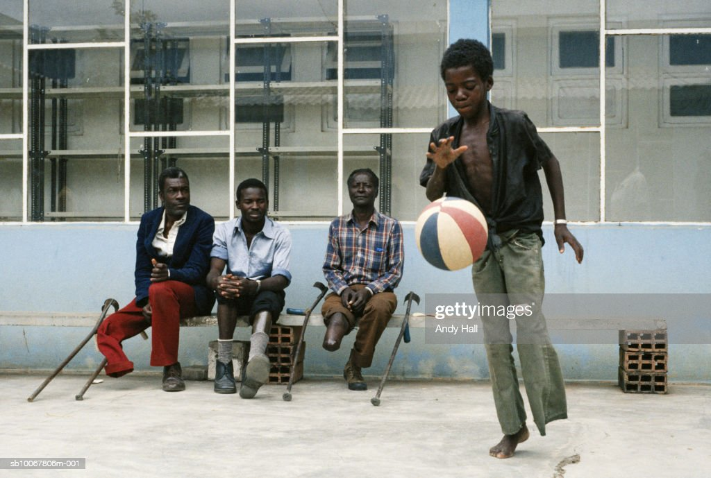 Angola, Huambo District, Artificial Limb Hospital, boy (10-11) playing basketball, men watching