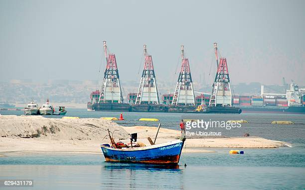 Angola. Luanda. Small moored fishing boat. With dredging and cargo ships in background.