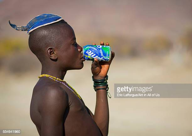 Angola Southern Africa Iona muhimba young man with traditional hairstyle drinkin a sprite can