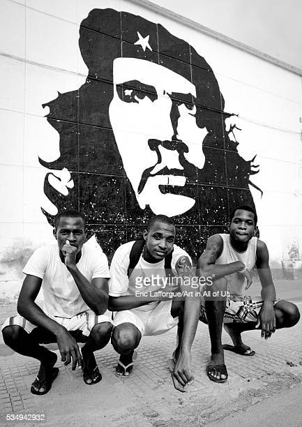 Angola Southern Africa Sumbe men crouched in front of a che guevara wall painting