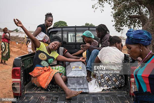 Women grieve over the casket of a young boy who had died two days prior The family said doctors had been uncertain whether the cause of death was...