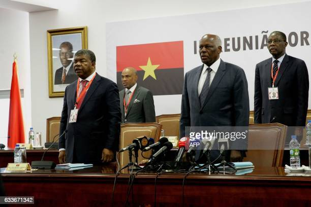 Angolan Defence Minister Joao Lourenco and Angolan President Jose Eduardo Dos Santos sing the party anthem during the ordinary meeting of the central...
