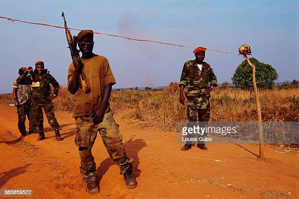 Angolan government soldiers stand guard at a roadblock that is marked with a human skull. After Angola gained independence from Portugal in 1975,...