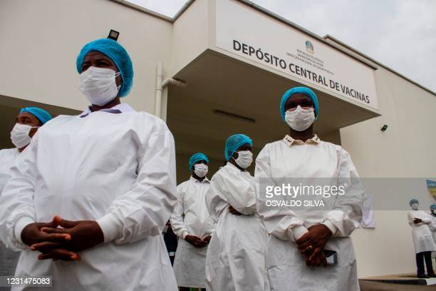 Angolan health workers stand outside the Central Vaccine warehouse where the first doses Oxford/AstraZeneca vaccines from India will be stored in...