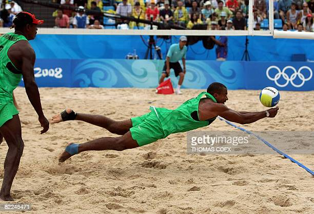 Angola's Emanuel Fernandes looks at teammate Morais Santos Abreu as he jumps to return the ball during their men's preliminary beach volleyball match...