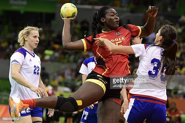 Angola's pivot Liliana da Silva Venancio jumps to shoot past Russia's left back Ekaterina Marennikova and Russia's left back Ekaterina Marennikova...