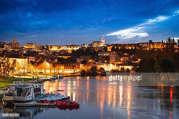 Angouleme : the city, the Charente river, the belfry and the city hall at night, viewed from the Houmeau harbour in which cruise barges are lying at...