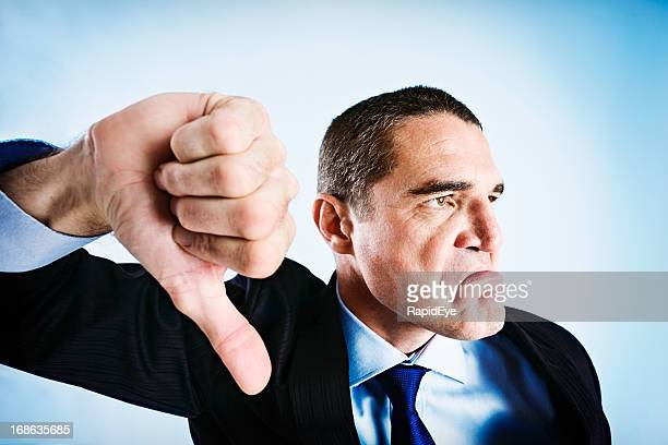 angrily frowning businessman makes thumbs-down signal - dismissal stock photos and pictures