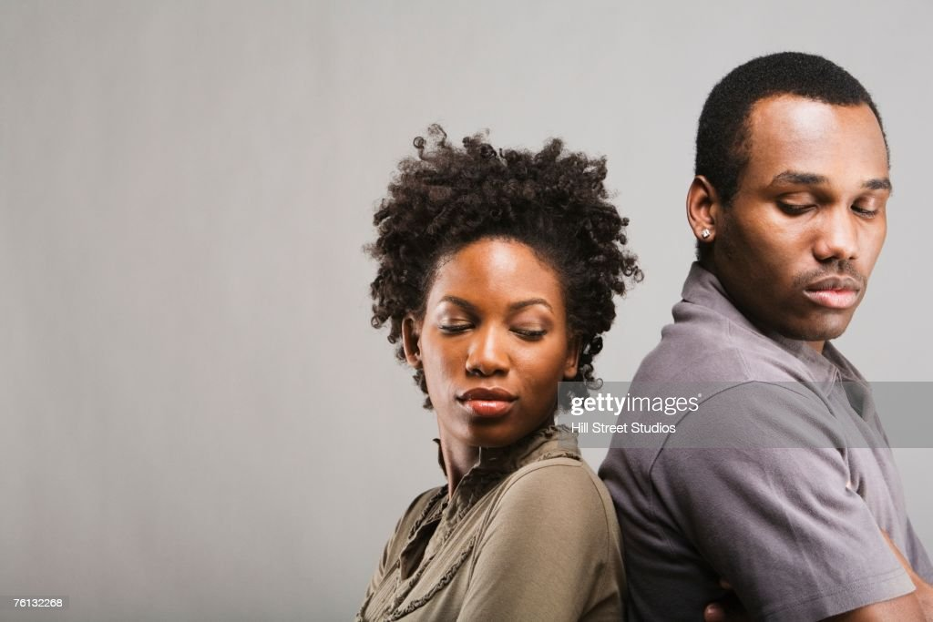 Angry African American couple standing back to back : Stock Photo