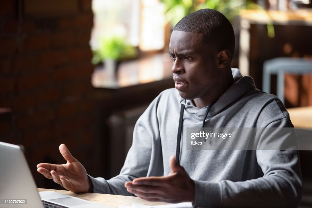 Angry African American man looking at laptop, receiving bad news : Stock Photo