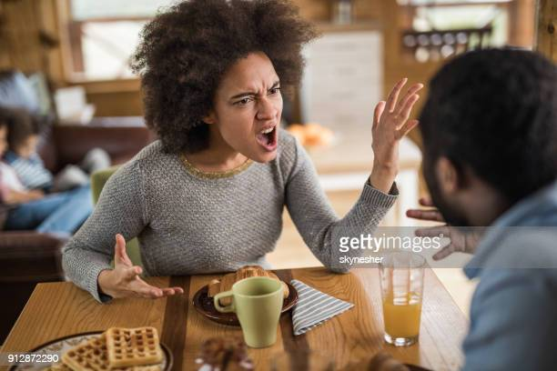Angry African American woman arguing with her husband at dining table.