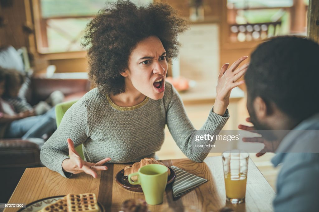 Angry African American woman arguing with her husband at dining table. : Stock Photo
