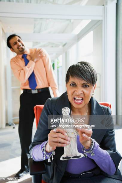 Angry African businesswoman holding voodoo doll of co-worker