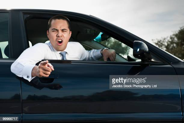 Angry Asian businessman shouting from car