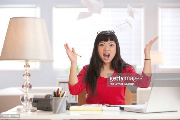 Angry Asian woman throwing papers in home office
