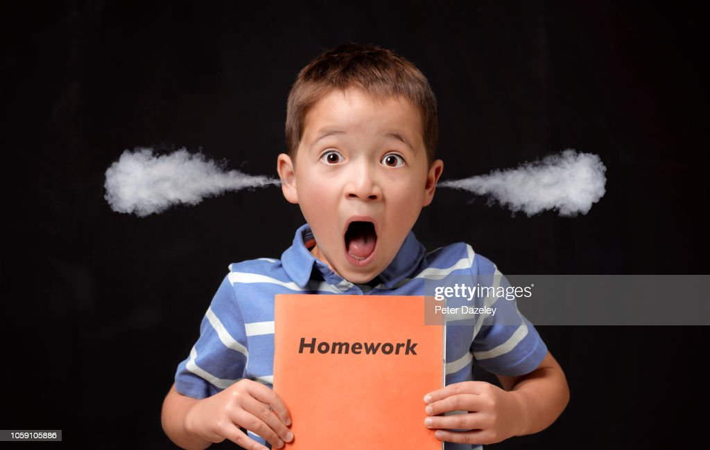 Angry boy holding his homework : Stock Photo