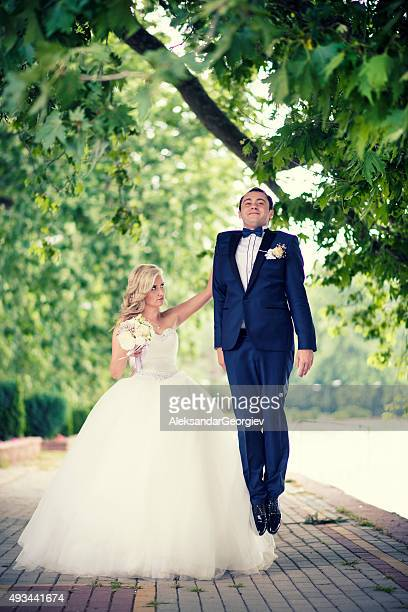 Angry Bride with one Hand holding the Groom in Air