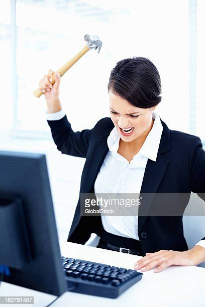 angry business lady hitting a computer keyboard with hammer - demolishing stock photos and pictures