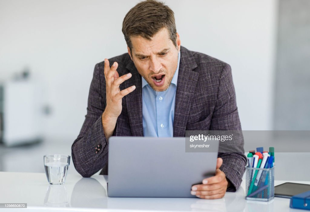 Angry businessman arguing during video call over computer in the office. : Stock Photo