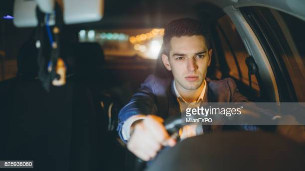 Angry businessman driving car at night