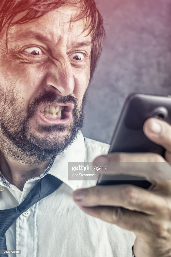 Angry businessman received frustrating SMS message : Stock Photo
