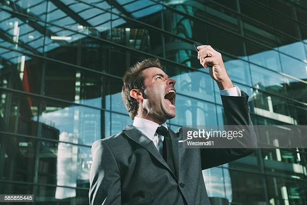 Angry businessman screaming at cell phone outside office building