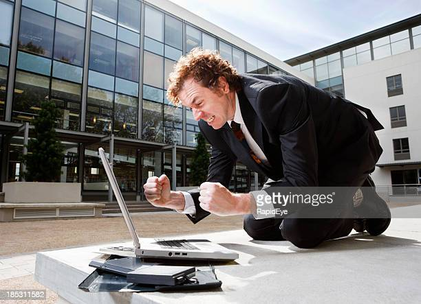 Angry businessman shakes his fists at laptop on the ground