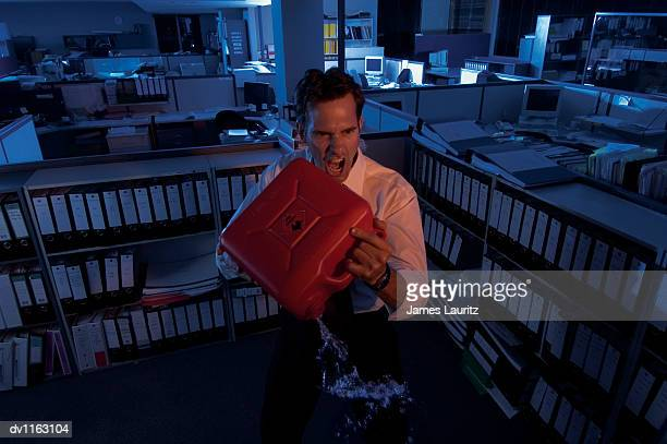 Angry Businessman Standing in an Open Plan Office Holding a Fuel Can and Pouring Petrol