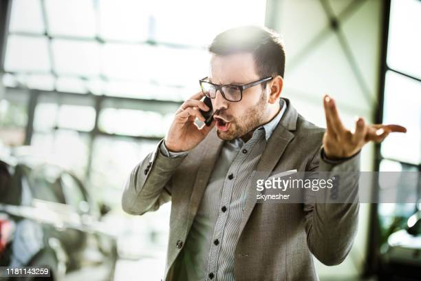 angry businessman talking on cell phone in a car showroom. - anger stock pictures, royalty-free photos & images