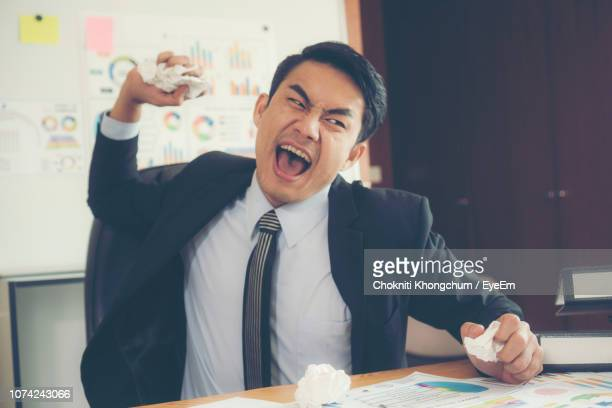 angry businessman throwing paper balls in office - throwing stock pictures, royalty-free photos & images