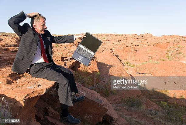 Angry Businessman with his laptop in desert