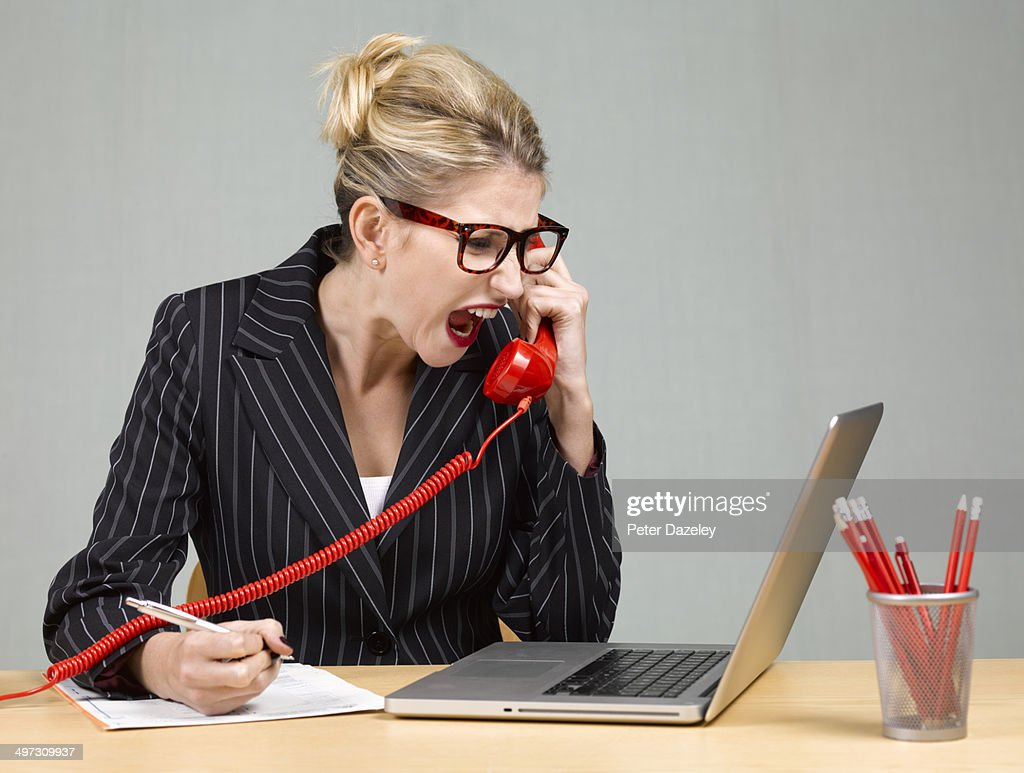 Angry businesswoman at desk : Stock Photo