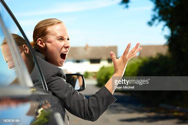 angry businesswoman in car screaming at another driver