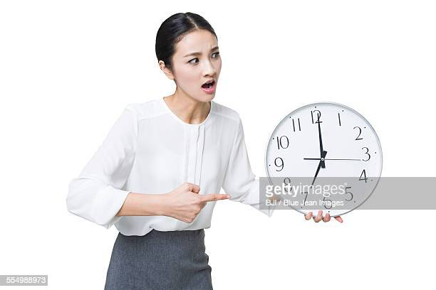 Angry businesswoman pointing at a clock
