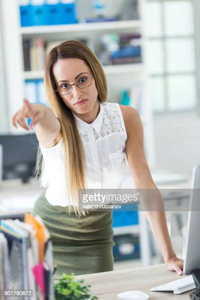 Angry businesswoman pointing at door