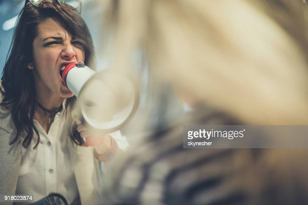 Angry businesswoman screaming at her subordinate colleague through megaphone.