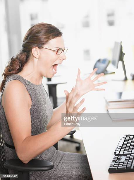 Angry businesswoman shouting at computer