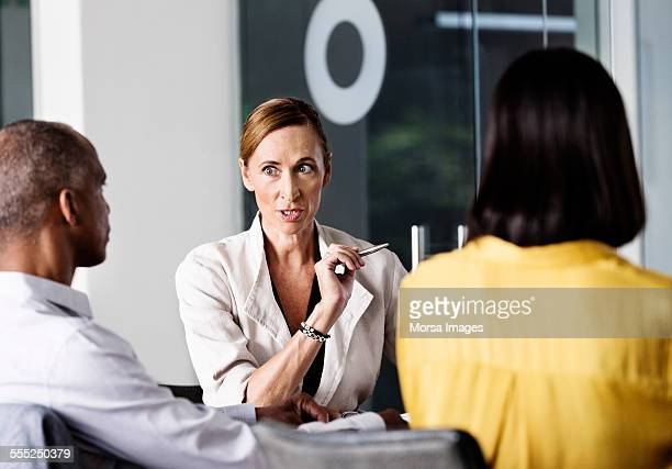 Angry businesswoman talking to colleagues