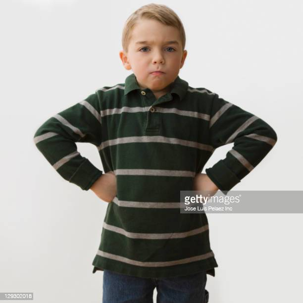 Angry Caucasian boy with hands on hips