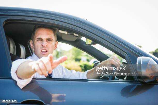 Angry Caucasian businessman shouting out car window